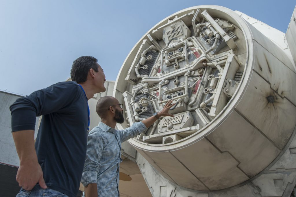 Imagineers looking at the Millennium Falcon at Star Wars: Galaxy's Edge.