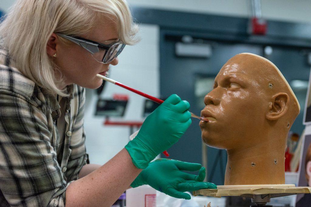 An Imagineer painting a sculpture model.