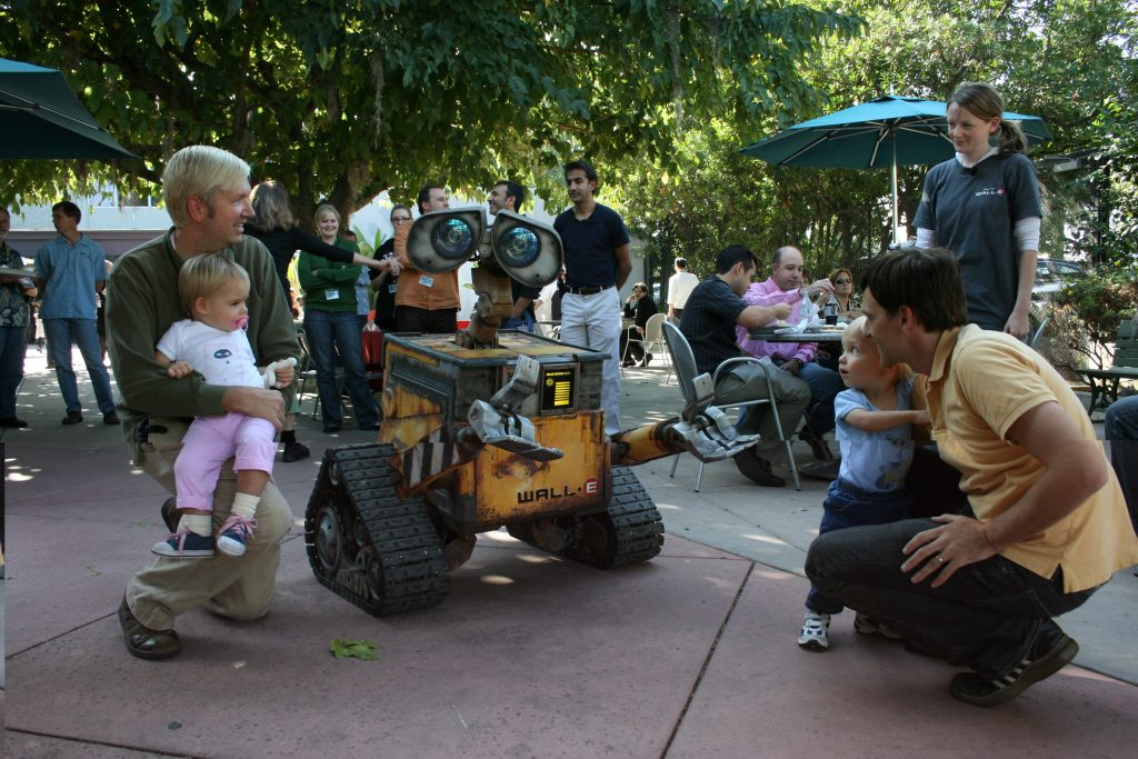 Imagineers and family interacting with the WALL-E animatronic figure.