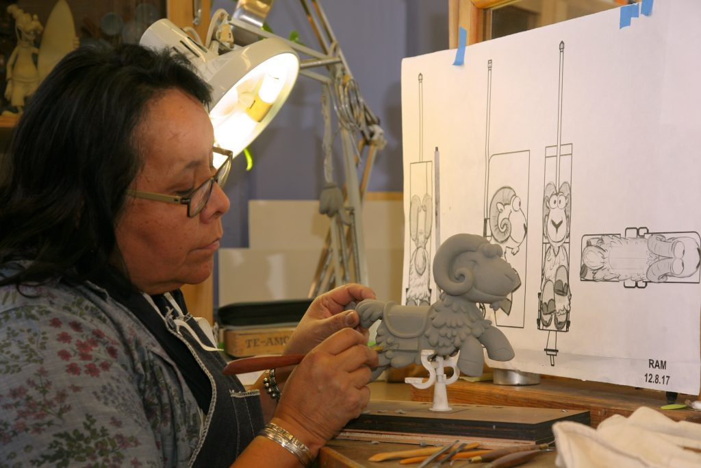 Imagineer sculpting a character for an attraction.