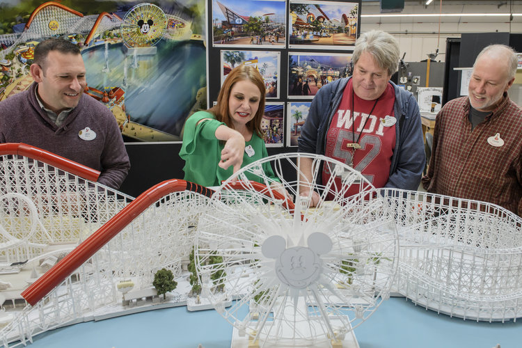 Imagineers looking at model of Pixar Pier.