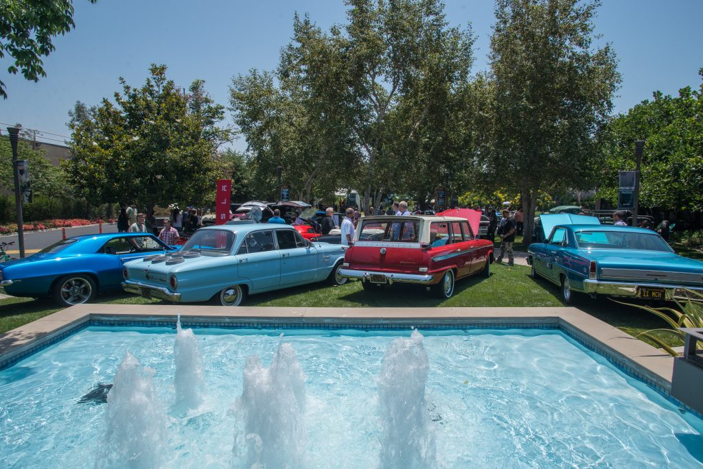 Imagineers exploring different classic cars at WDI's Car Show.