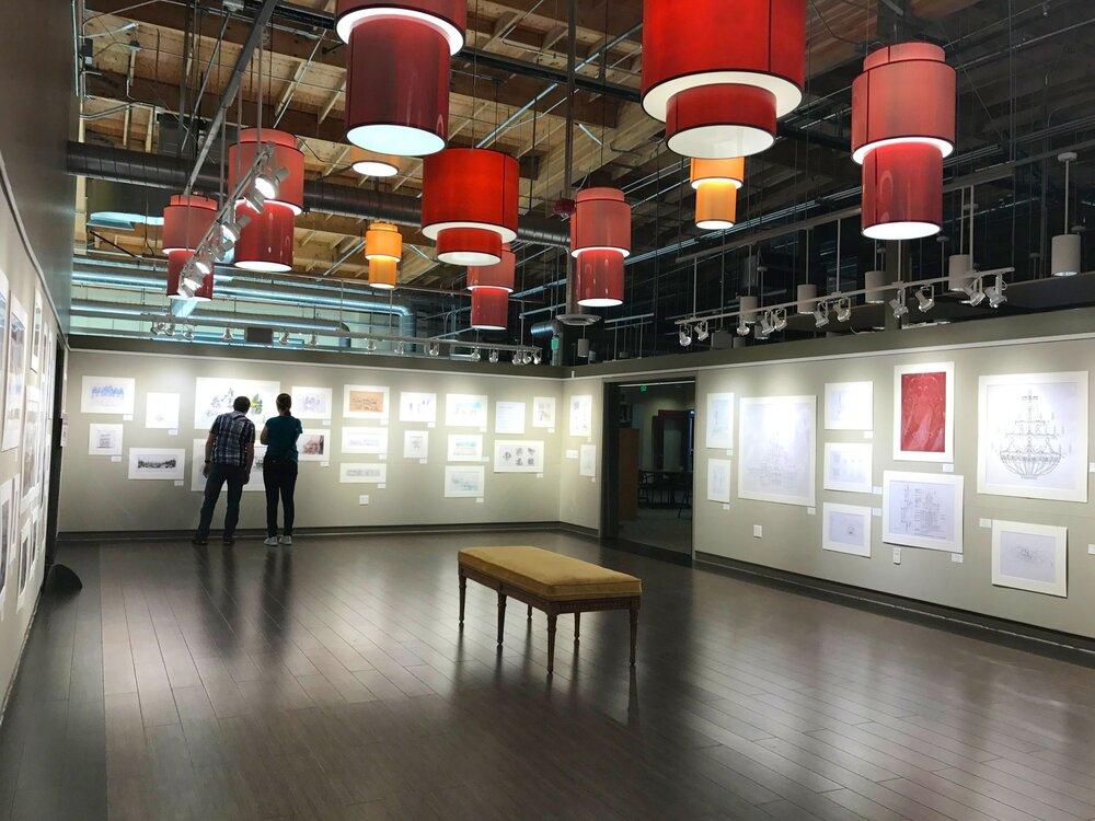 Imagineers looking at legacy artwork in a gallery.
