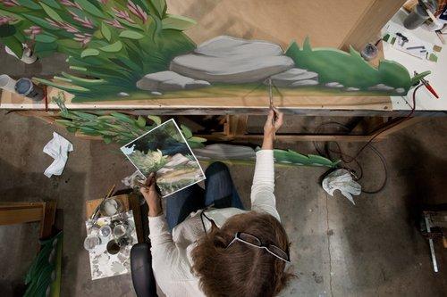 Imagineer painting a mural.