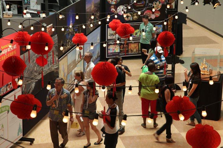 Imagineers observing models and concept art for Shanghai Disney Resort.
