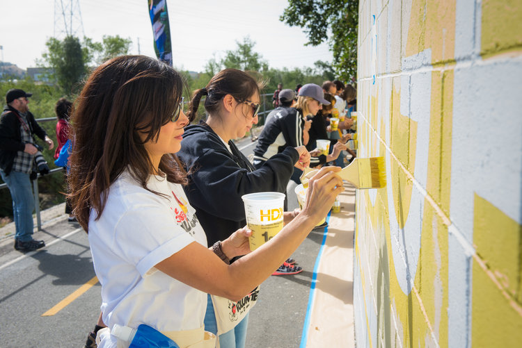 Imagineers painting a wall during a VoluntEARS event.