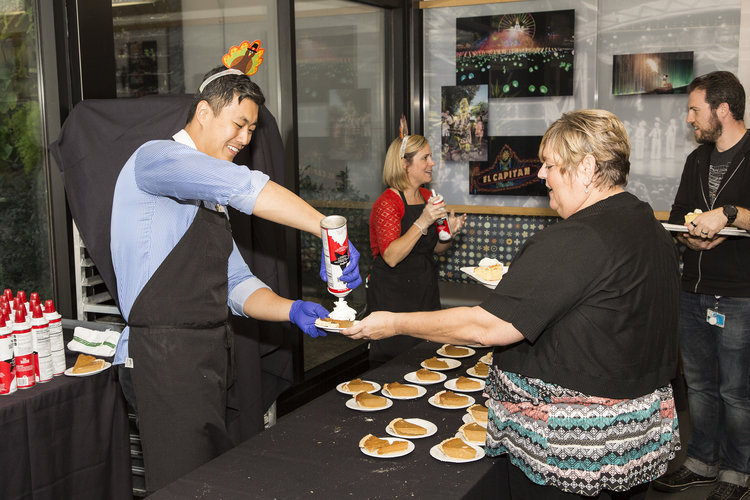 Imagineers serving and receiving pie at the Thanksgiving event on the WDI campus.