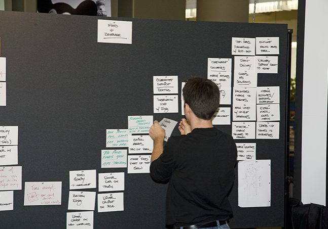 Imagineers working on a concept board.