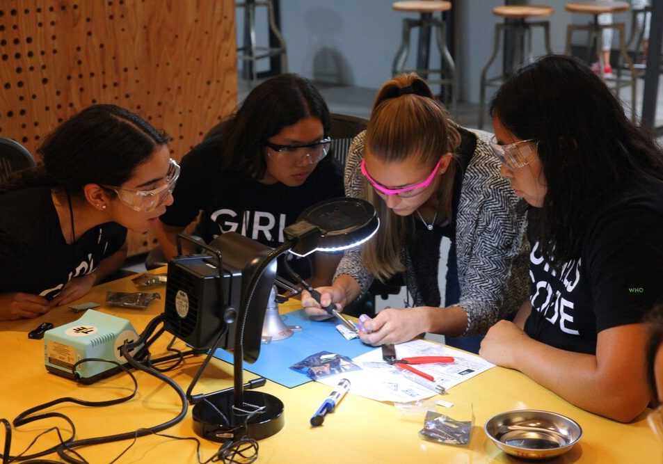 Girls who Code participants practicing soldering during WDI tour.