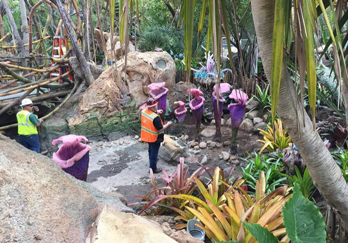 Imagineer installing props to an attraction.