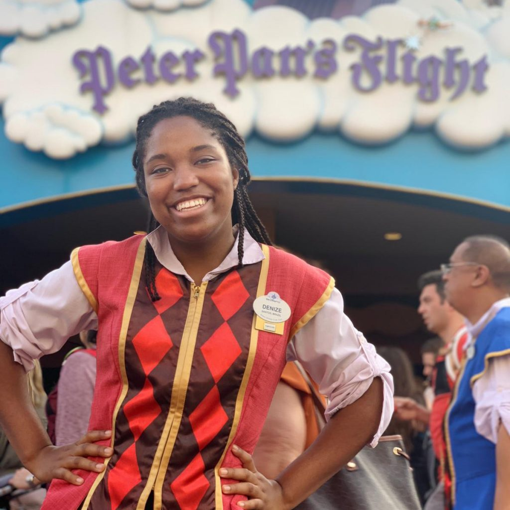 A participant stands in costume in front of the sign for Peter Pan's Flight at Magic Kingdom Park