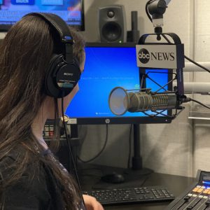 A Professional Intern sits in front of an ABC News microphone with a headset on