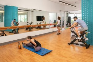 Participants do yoga, ride a bike, and lift weights in one of Flamingo Crossing Village's fitness rooms