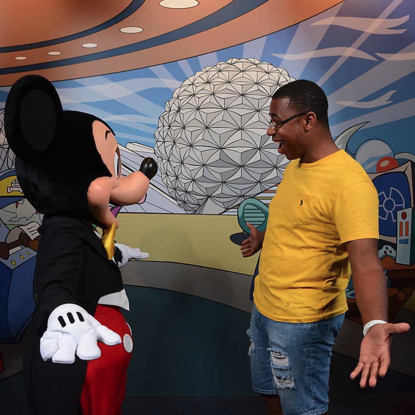 A participant throws his arms wide and smiles as he meets Mickey Mouse