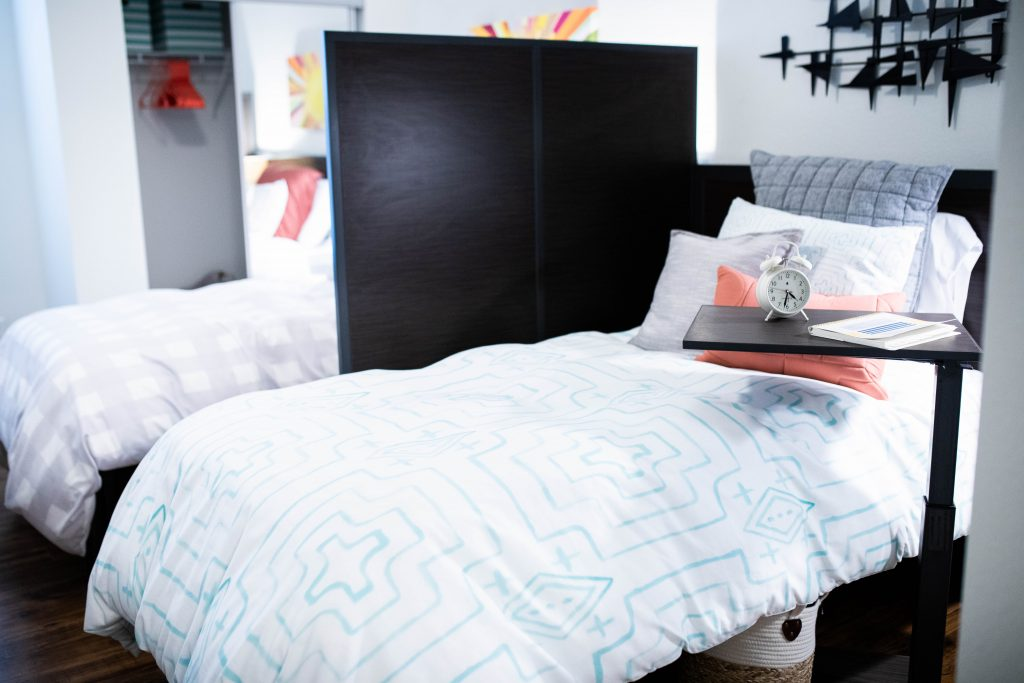 Two extra-long twin beds separated by a privacy divider and a night stand