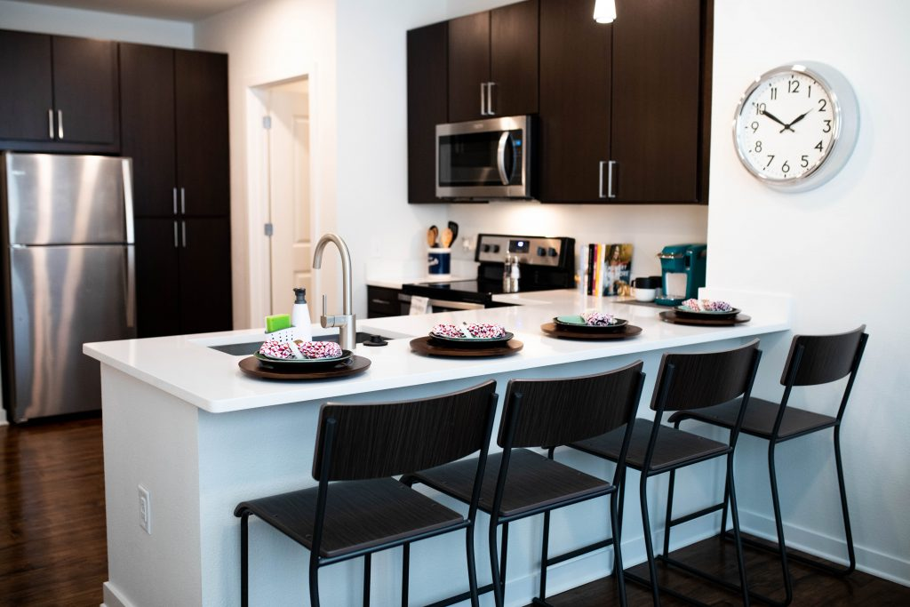 A view of the kichen's cabinets, microwave, counter, and counter stools from the living room